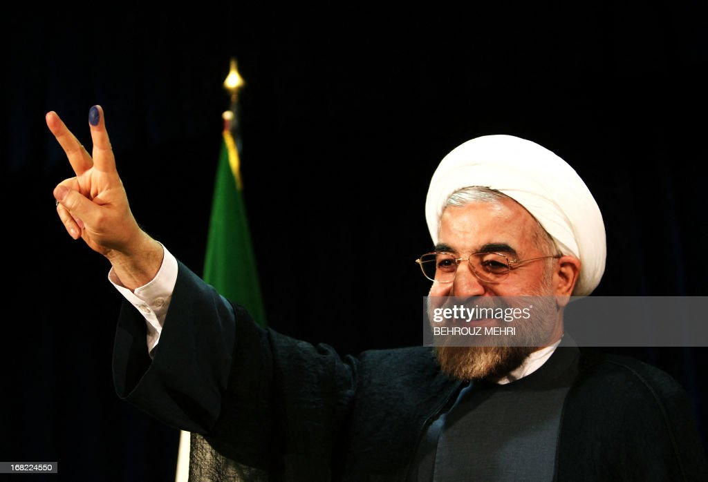 Iran's former top nuclear negotiator Hassan Rowhani flashes a victory sign after registering his candidacy for the upcoming presidential election at the interior ministry in Tehran on May 7, 2013. Iran began a five-day registration period for candidates in Iran's June 14 presidential election, with a string of conservative hopefuls in the running but with key reformists yet to come forward, media reports said. AFP PHOTO/BEHROUZ MEHRI