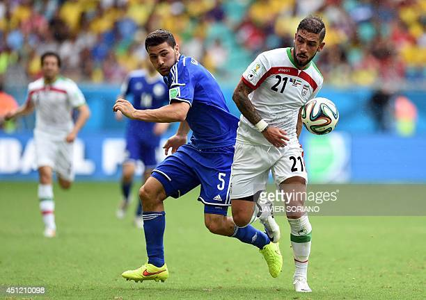 Iran's forward Ashkan Dejagah and BosniaHerzegovina's defender Sead Kolasinac vie for the ball during a Group F football match between...
