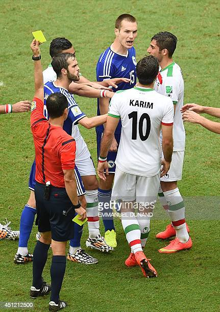 Iran's forward Karim Ansari Fard is shown the yellow card by referee Carlos Velasc Carballo of Spain during a Group F football match between...