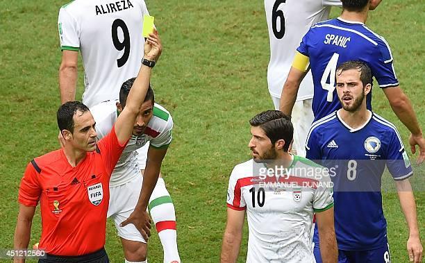 Iran's forward Karim Ansari Fard is shown the yellow card by referee Carlos Velasc Carballo of Spain as BosniaHerzegovina's midfielder Miralem Pjanic...