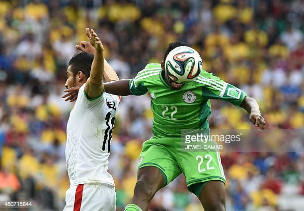 Iran's forward Reza Ghoochannejhad challenges Nigeria's defender Kenneth Omeruo as he heads the ball during the Group F football match between Iran...
