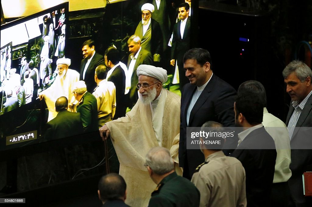 Iran's head of the Assembly of Experts, Ahmad Jannati (C), walks past a TV screen as he attends the opening session of the new parliament in Tehran on May 28, 2016. Iranian parliamentarians met in Tehran for the first time since elections finished in April. KENARE