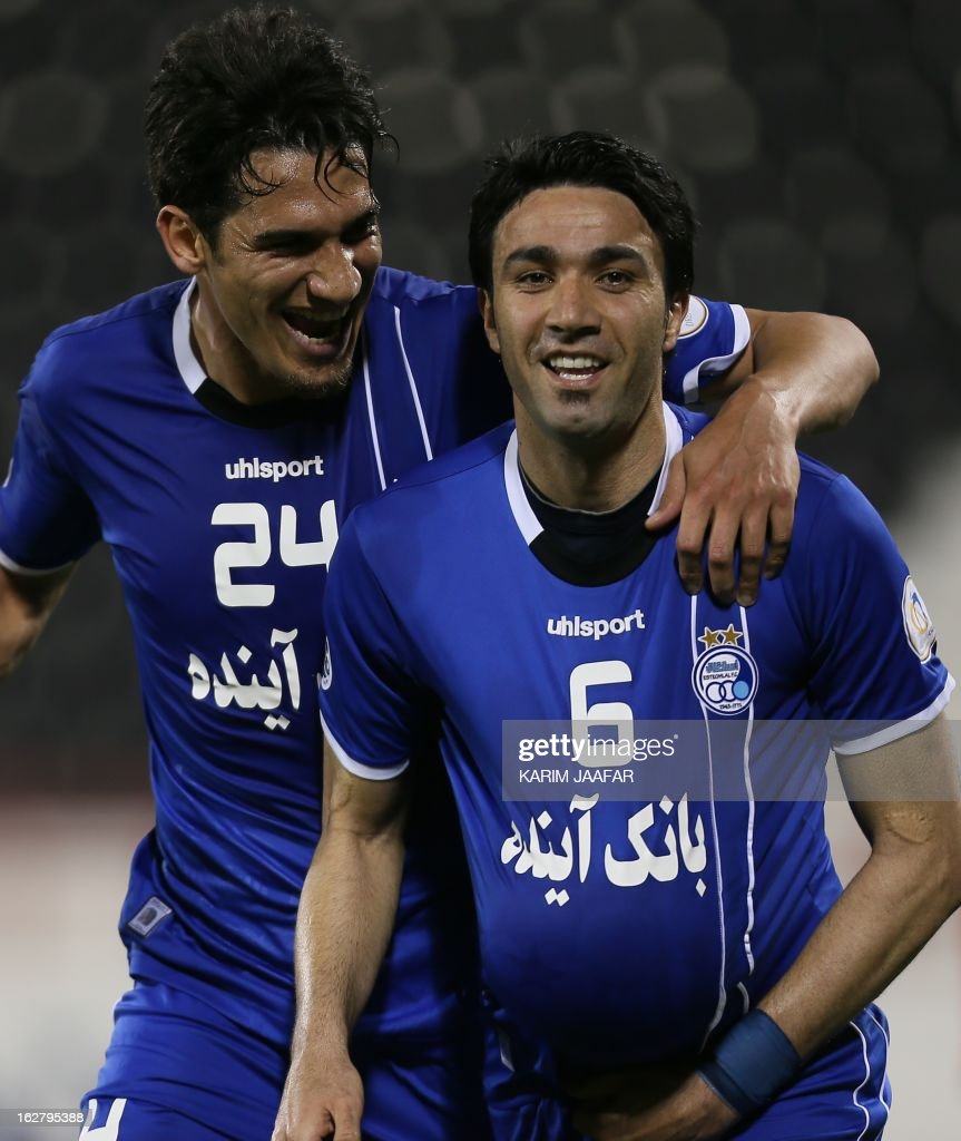 Iran's Javad Nekonam (R) celebrates with his teammate after scoring a goal during the AFC Champions League football match Iran's Esteghlal versus Qatar's al-Rayyan clubs in the Qatari capital Doha on February 27, 2013.