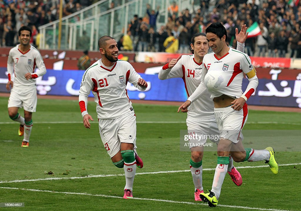 Iran's Javad Nekounam (R) celebrates after scoring a goal against Lebanon during their 2015 AFC Asian Cup group B qualifying football match at the Azadi Stadium in Tehran, on February 6, 2013 Iran won the match 5-0. AFP PHOTO/ATTA KENARE