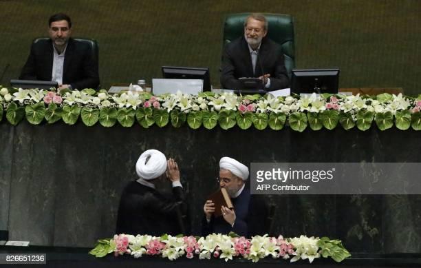 Iran's Judiciary Chief Sadeq Larijani waves to Parliament Speaker Ali Larijani during the swearingin ceremony of President Hassan Rouhani before...