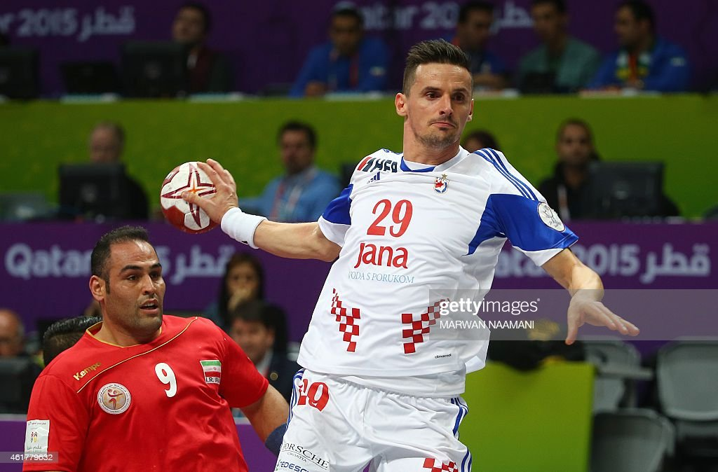 Iran's Mahdi Bijari (L) looks on as Croatia's Ivan Nincevic attempts a shot on goal during the 24th Men's Handball World Championships preliminary round Group B match between Croatia and Iran at the Duhail Handball Sports Hall in Doha on January 19, 2015. AFP PHOTO / MARWAN NAAMANI