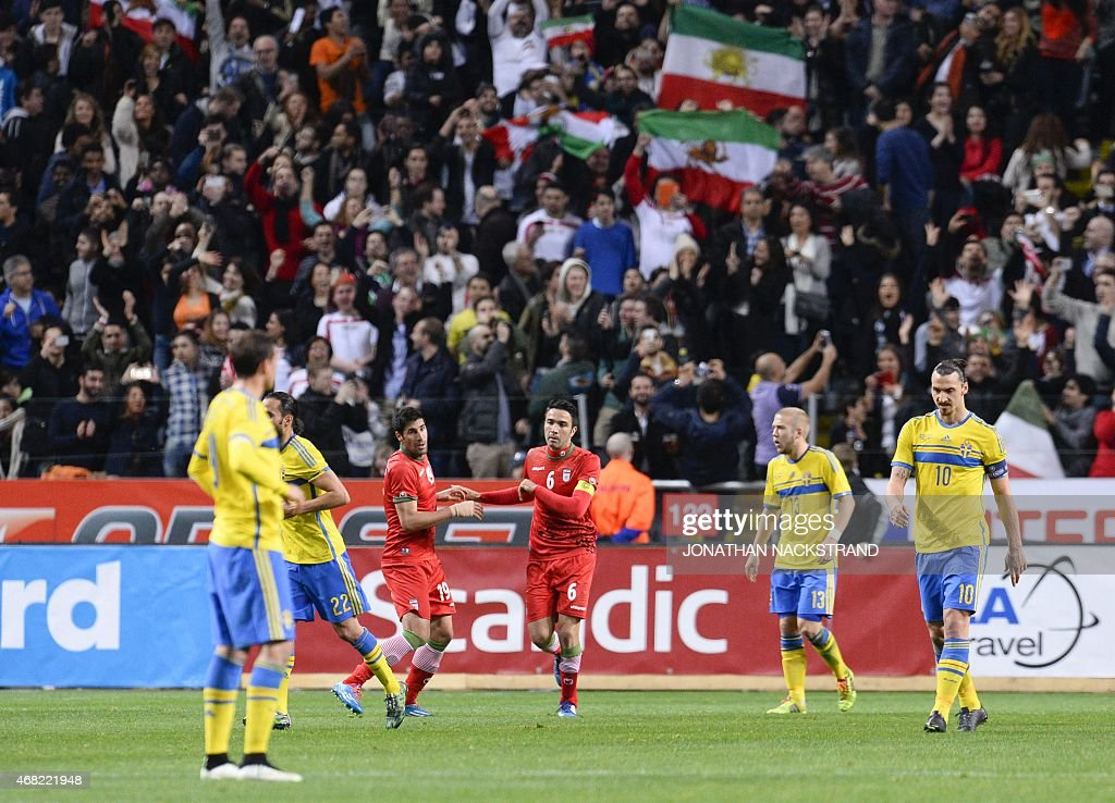 Iran's midfielder Javad Nekounam (3rd-R) celebrates with his teammate defender Hashem Beikzadeh after scoring a goal during the friendly international football match between Sweden and Iran at the Friends Arena in Solna near Stockholm on March 31, 2015.