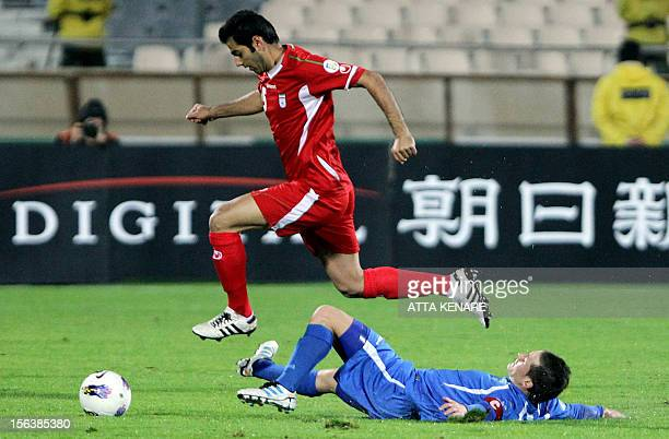 Iran's Pejman Montazeri jumps over Uzbekistan's Server Djeparov as he advances with the ball during their 2014 World Cup Asian zone group A...