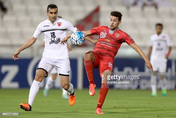 Iran's Persepolis FC defender Mohsen Nodehi and Qatar's Lekhwiya FC's Youssed Mskakni vie for the ball during the AFC Champions League football match...