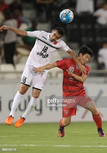 Iran's Persepolis FC defender Mohsen Nodehi and Qatar's Lekhwiya SC midfielder Nam Taehee vie for the ball during the AFC Champions League football...
