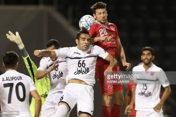 Iran's Persepolis FC defender Shahab Karami and Qatar's Lekhwiya SC midfielder Youssef Mskani jump to head the ball during the AFC Champions League...