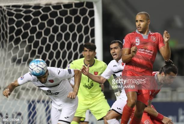 Iran's Persepolis FC forward Mehdi Taremi clears the ball as Qatar's Lekhwiya SC forward Youssef ElArabi looks on during the AFC Champions League...