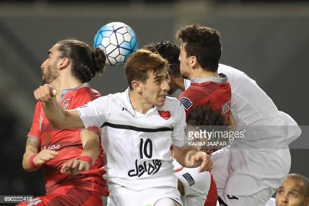 Iran's Persepolis FC midfielder Farshad Ahmadzadeh vies for the ball against Qatar's Lekhwiya SC midfielder Youssef Msakni and defender Chico Flores...