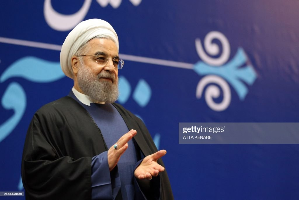 Iran's President Hassan Rouhani applauds after awarding the defence and foreign ministers, as well as the country's atomic chief with the Medal of Honour for their role in the implementation of a nuclear deal with world powers, on February 8, 2016, in Tehran. / AFP / ATTA KENARE
