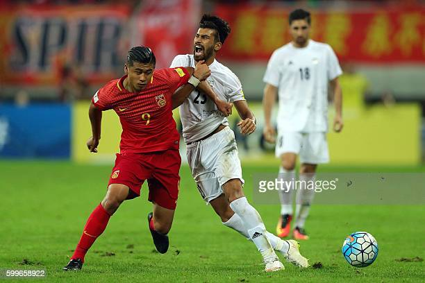 Iran's Ramin Rezaeian fights for the ball with China's Zhang Yuning during their 2018 World Cup qualifying football match in Shenyang northeast...