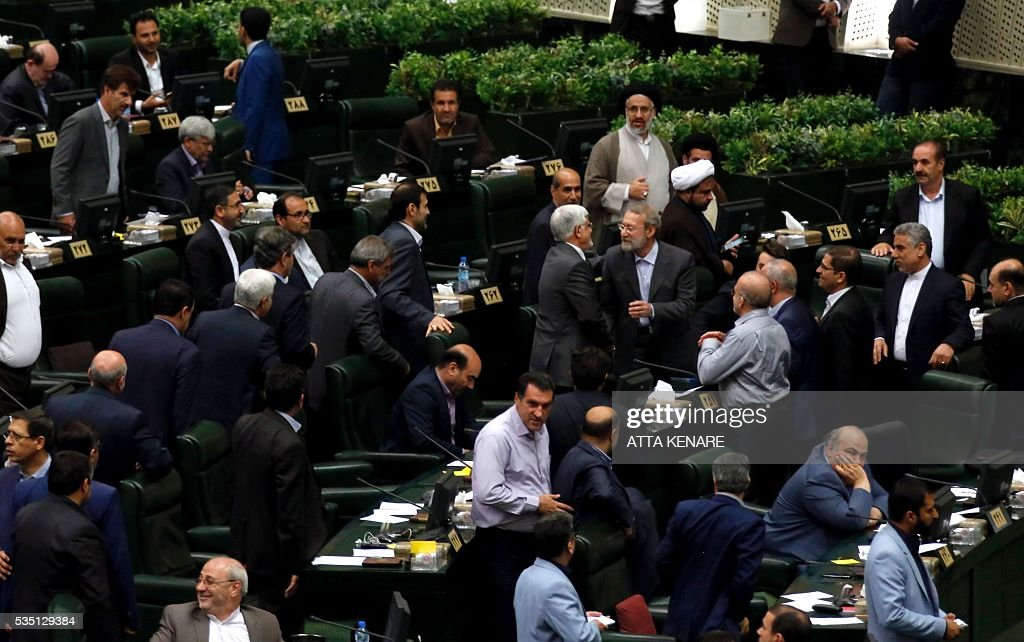 Iran's re-elected Parliament speaker Ali Larijani (R) is congratulated by MPs following the announcment of the results during a parliament session in Tehran on May 29, 2016. Larijani, a moderate conservative, retained the speakership of Iran's parliament despite major gains for reformists in February elections, benefiting from credit gained by his support for last year's nuclear deal. / AFP / ATTA