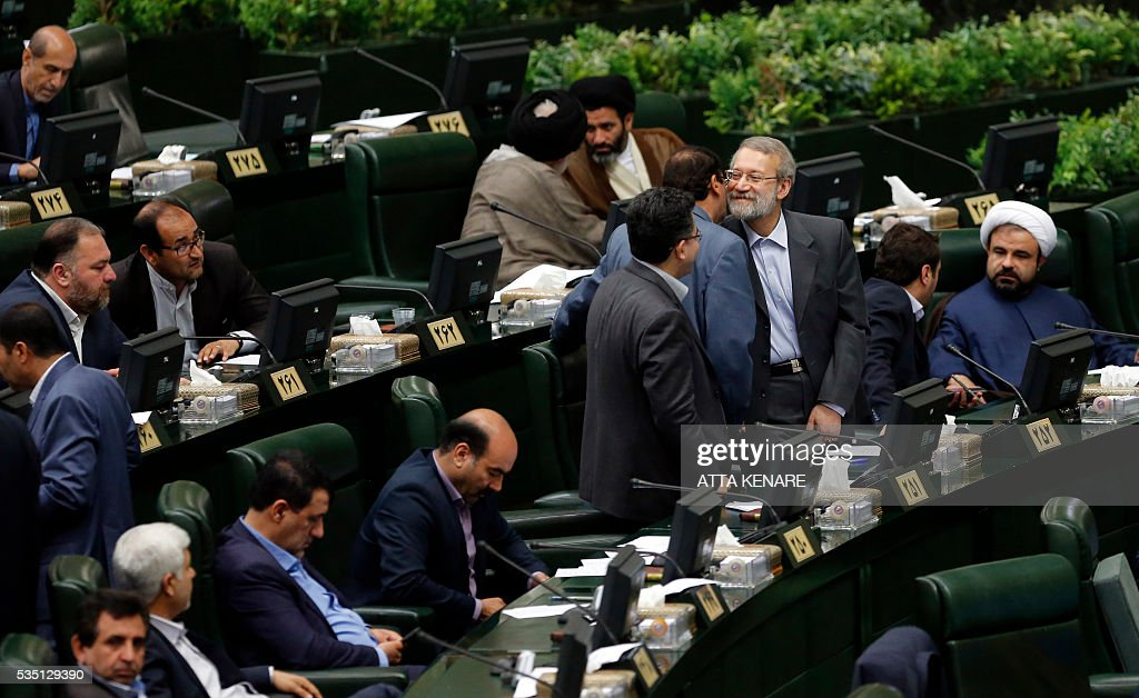 Iran's re-elected Parliament speaker Ali Larijani (3rd-R) is congratulated by MPs following the announcment of the results during a parliament session in Tehran on May 29, 2016. Larijani, a moderate conservative, retained the speakership of Iran's parliament despite major gains for reformists in February elections, benefiting from credit gained by his support for last year's nuclear deal. / AFP / ATTA