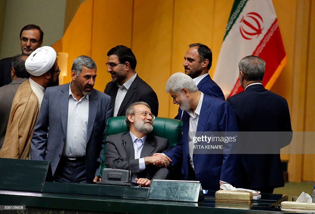 Iran's re-elected Parliament speaker Ali Larijani (C) is congratulated by MPs following the announcment of the results during a parliament session in Tehran on May 29, 2016. Larijani, a moderate conservative, retained the speakership of Iran's parliament despite major gains for reformists in February elections, benefiting from credit gained by his support for last year's nuclear deal. / AFP / ATTA