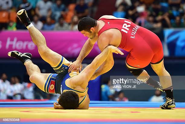 Iran's Reza Yazdani competes with Kyrgyzstan's Magomed Musaev in the men's freestyle 97 kg wrestling event for the gold medal during the 2014 Asian...