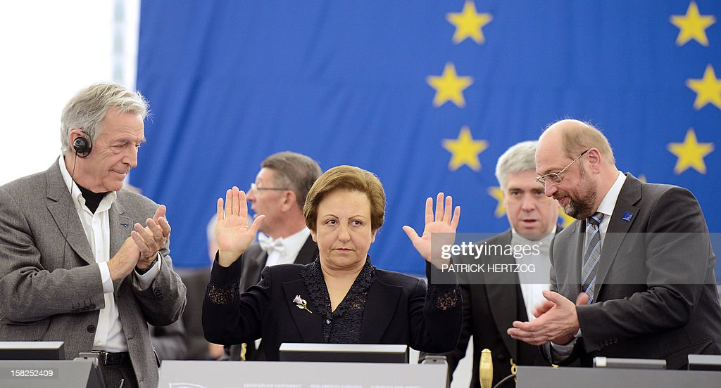 Iran's Shirin Ebadi (C), Nobel Peace laureate in 2003, President of the European Parliament Martin Schulz (R) and Greek-French film director Costa-Gavras attend a ceremony awarding the Sakharov Prize for freedom of thought to Iranian activists, lawyer Nasrin Sotoudeh and film director Jafar Panahi, at the European Parliament in Strasbourg, eastern France, on December 12, 2012. The laureates were not able to attend the ceremony as they were not allowed to leave Iran. AFP PHOTO / PATRICK HERTZOG