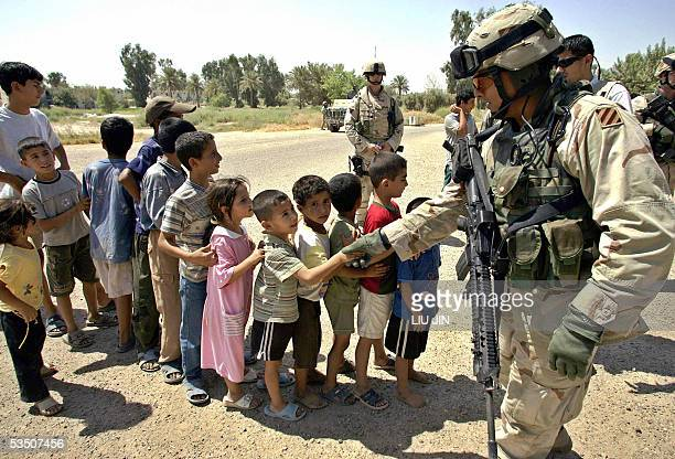A Iraqi boy shakes hands with a US soldier during the Food Distribution Mission operated by Alpha Company 425th Civil Affairs Company and 304th PYSOP...