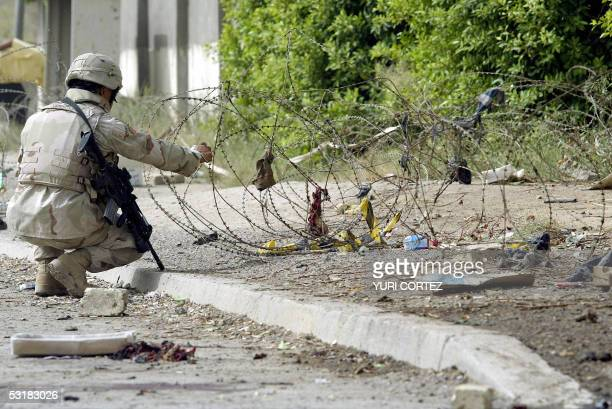 A US soldier inspects 02 July 2005 the scene where a suicide bomber blew himself up among recruits to the Iraqi security forces near AlNusur Square...