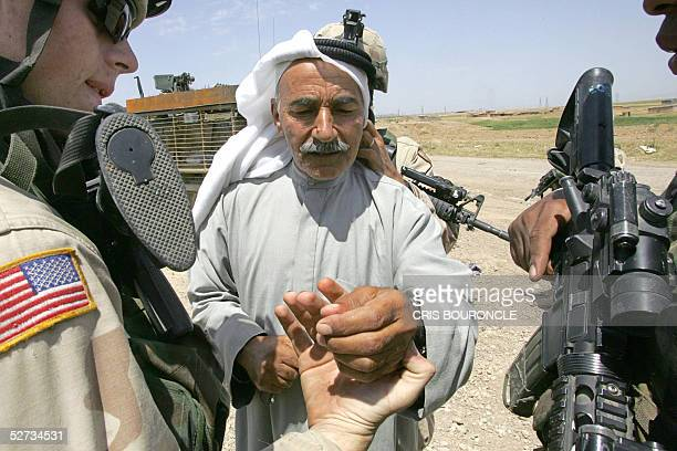 An Iraqi elderly man is examined for tattoos that would link him to insurgent factions when he was stopped at a roadblock set by US Army soldiers...