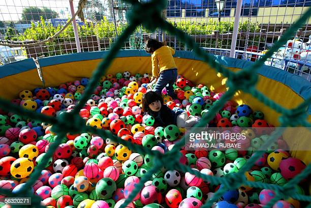 An Iraqi girl plays in a pool filled with colorful balls at alJadriyah club in Baghdad during a bazaar organized by members of the Ma'an Coalition...