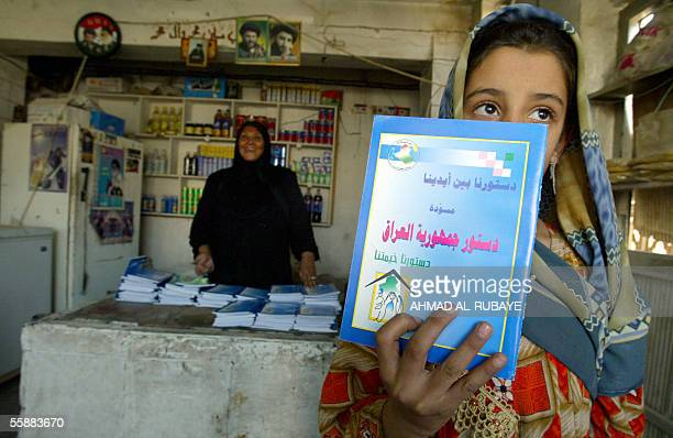 An Iraqi girl shows a copy of draft constitution she received from a food distributor in Baghdad's poor Sadr city neighborhood 09 October 2005 More...