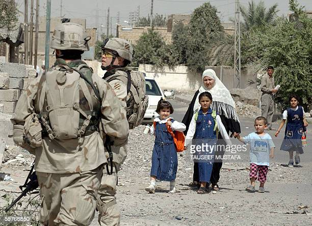 An Iraqi woman and her children walk past US soldiers from the Alfa Company 2/7 infantries division during a patrol in Tikrit 170 kms north of...