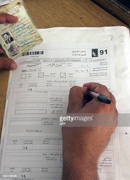 An official fills out the form of an applicant at the registration center in the Dubat neighborhood of the western city of Fallujah securing his...