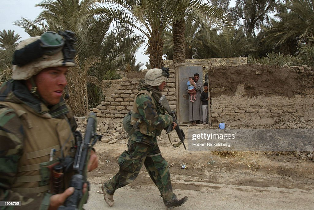 Iraq civilians watch as US Marines of the 1st Marine Division jog past through a street March 30 2003 of Tahrir Iraq which is approximately 100 km...