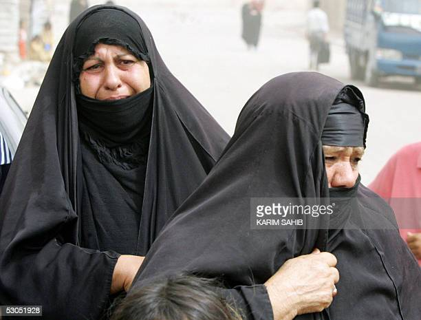 Iraqi woman cry as they watch the van carrying the coffin of 22yearold Alaa and her unborn baby drive away in the AlShula district of Baghdad 11 June...