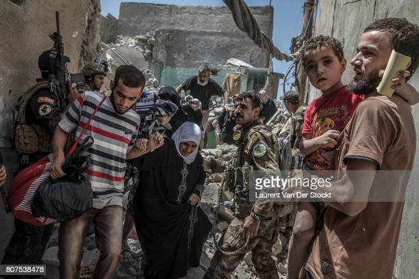 Iraq soldiers escort civilians who emerge from the ruined buildings of alNuri mosque complex in Mosul Iraq on June 29 2017 The Iraqi Army Special...
