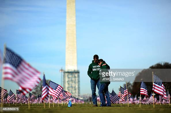 Iraq war veteran couple Colleen Ryan and Jeff Hensley of the US Navy comfort each other as they help set up 1892 American flags on the National Mall...