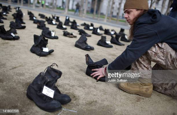 Iraq war veteran Scott Olsen adjusts rows of combat boots that are part of the 'Eyes Wide Open' exhibit in front of San Francisco City Hall on March...