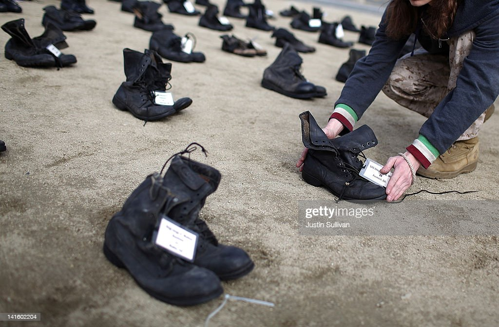 Iraq war veteran <a gi-track='captionPersonalityLinkClicked' href=/galleries/search?phrase=Scott+Olsen&family=editorial&specificpeople=592272 ng-click='$event.stopPropagation()'>Scott Olsen</a> adjusts rows of combat boots that are part of the 'Eyes Wide Open' exhibit in front of San Francisco City Hall on March 19, 2012 in San Francisco, California. The Eyes Wide Open exhibition includes a pair of boots for every one of the 481 California servicemen and women who died in the Iraq war.