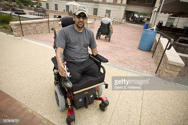 Iraq war veteran SGT Luis RosaValentin who lost both of his legs left arm and hearing while serving in Iraq rolls past the Mologne House where he is...
