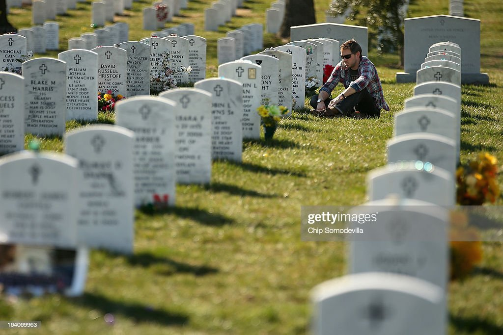 Iraq war veteran U.S. Marine Corps Corporal (retired) Ryan Lamke visits the grave of friend and fellow Marine Corporal Benny G. Cockerham III on the 10th anniversary of the start of the Iraq war at Arlington National Cemetery March 19, 2013 in Arlington, Virginia. Lamke lives in Washington, DC, and makes a point to visit Cockerham's grave once a month and made this visit specifically because of the anniversary. Marine Captain Tyler B. Swisher and HM3 Christopher Thompson were also killed with Cockerham when their vehicle was hit with an IED on Oct. 21, 2005 in Al Amariyah, Iraq.