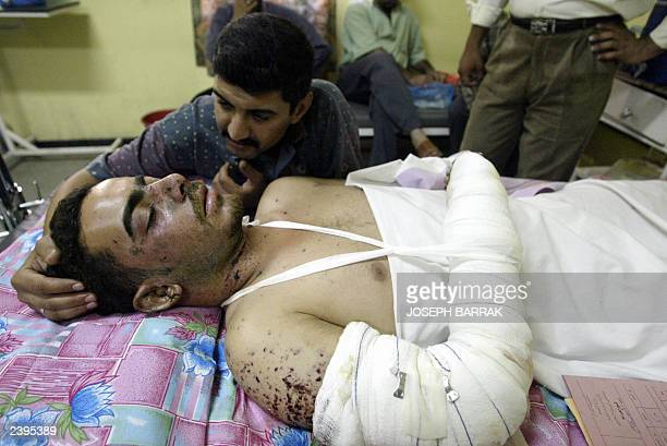 Iraqi Ali comforts his wounded cousin Mohammed Salah Joumma 08 August 2003 at alYarmouk hospital in Baghdad Joumma was wounded 07 August when a car...