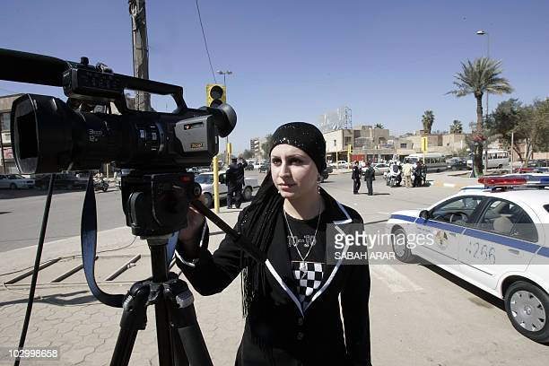 Iraqi alIqtisadiyah TV channel reporter Hoda Haddad looks through the viewfinder of a camera as she works on a report in central Baghdad on March 6...