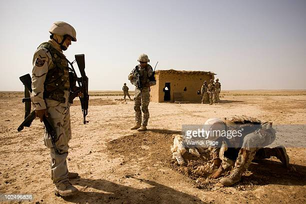 Iraqi and US forces search a suspected arms cache during a village clearance operation on June 12 2010 in Ali Juma Diyala Province Iraq Iraq faces...