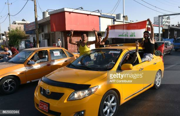 Iraqi Arabs and Turkmen celebrate after Iraqi forces advanced in Kirkuk during an operation against Kurdish fighters on October 16 2017 Iraqi forces...