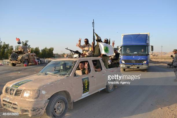 Iraqi armed forces and Peshmerga forces pose in a car flashing victory signs on the Kirkuk Baghdad road in Suleiman Bey town of Tuz Khurmato Iraq on...