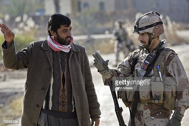 Iraqi Army 1st Lt Alla Sadiq speaks with a local resident as Iraqi troops sweep through a neighborhood on the outskirts of Ramadi January 18 2007 in...