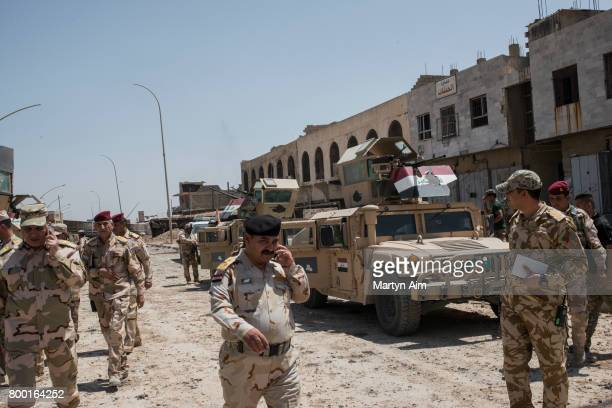 Iraqi Army commanders and soldiers outside an Islamic State drone and IED factory discovered today on June 23 in the frontline neighbourhood of...