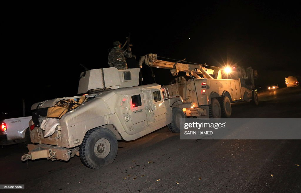 Iraqi army soldiers drive armoured vehicles towards Makhmur, about 280 kilometres (175 miles) north of the capital Baghdad, on February 11, 2016. The Iraqi army is deploying thousands of soldiers to a northern base in preparation for operations to retake the Islamic State (IS) group's hub of Mosul, according to officials, as IS still holds Fallujah, east of Ramadi, and Mosul, Iraq's second city that is located in the north. / AFP / SAFIN HAMED