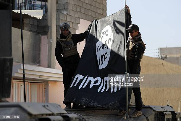 Iraqi army soldiers hold a flag from the Islamic State jihadist group upsidedown in a northeastern district of the city of Mosul on November 24 2016...