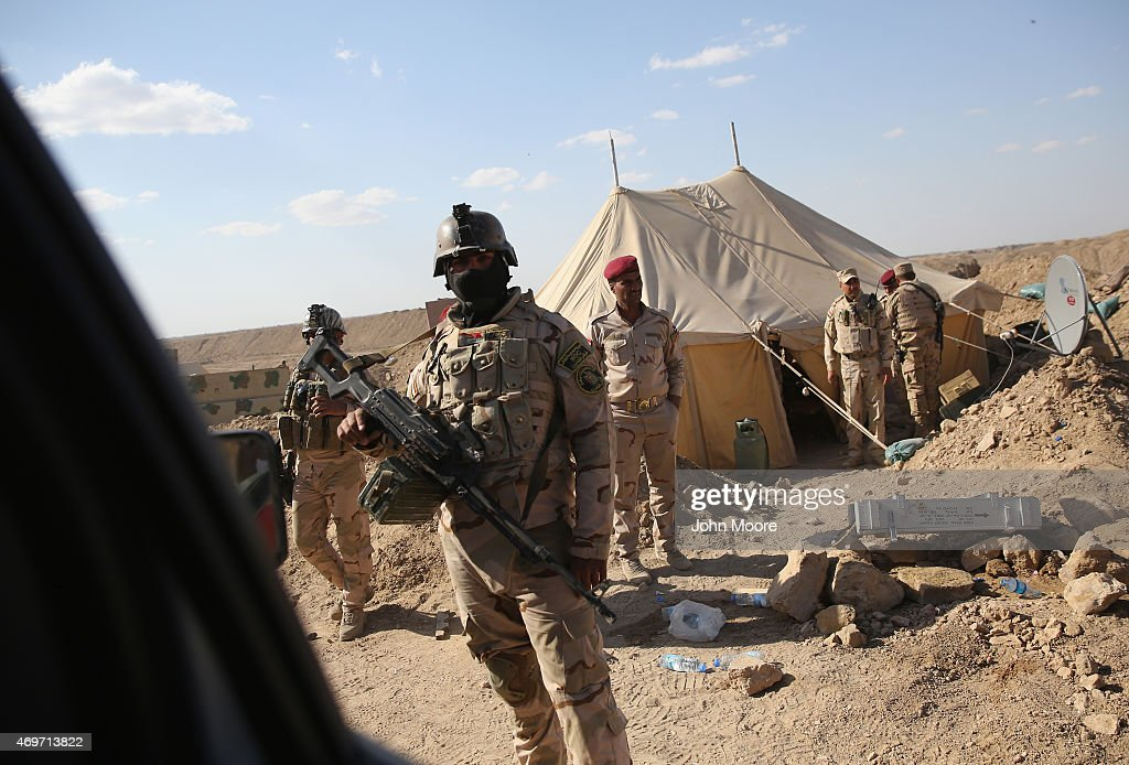 Iraqi Army troops stand near the frontline with ISIL fighters on April 14 2015 near AlKarmah in Anbar Province Iraq Iraqi government forces are...