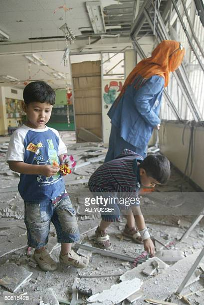 Iraqi boys collect flowers from the ruins of their classroom while their teacher looks at shattered windows on April 22 2008 A Katiyusha rocket aimed...
